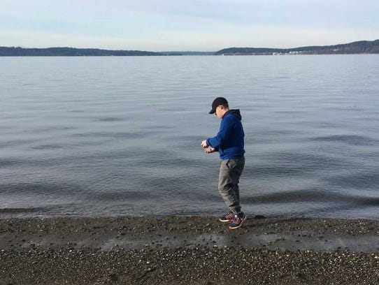 A volunteer gathers a water sample for the microplastic