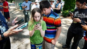 Pokémon Go players Thompson Childress, 11, (right) and Alex Landrigan, 11, (left) collect a pocket monster during a raid at Levitt Shell, Thursday afternoon. The virtual game that swept the world two-years ago is still going strong. Recent updates have made it possible to turn the game into a platform where people can battle together on the field and form friendships.