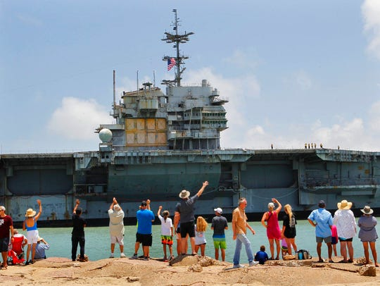 Spectators wave as the USS Independence is towed past