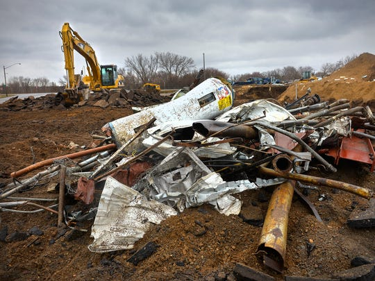 A debris pile sits near an excavator working to remove the parking lot at the former El Paso club site, 200 Second Ave. NW, St. Joseph. The site is planned for a new Kwik Trip convenience store.