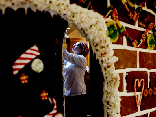 Jackie Henry, a sous chef at Embassy Suites in Loveland, helps to put the finishing touches on a life-size gingerbread house.