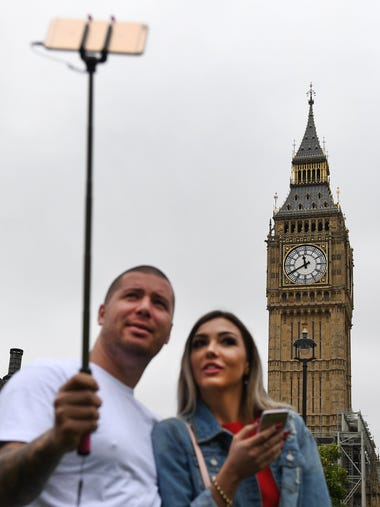 A couple takes selfies of the Queen Elizabeth tower