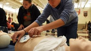 A student learns how to use a defibrillator at Dumont High School's third annual Wellness Fair on Wednesday.