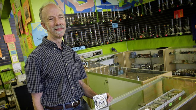 David Kelly, owner of Atomic Glass, displays a variety of synthetic marijuana products for sale at the store in 2010.