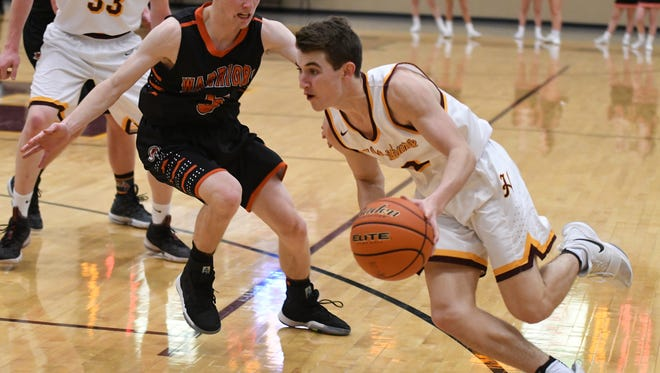 Harrisburg's Nick Hoyt (2) drives to the hoop past Sioux Falls Washington's Topher Zahn in varsity action Friday night in Harrisburg. Hoyt led all scoring with 19 points as No.1 Harrisburg won 69-59.
