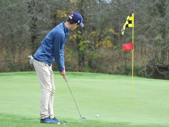Jack McElligott putts toward the cup on the third hole