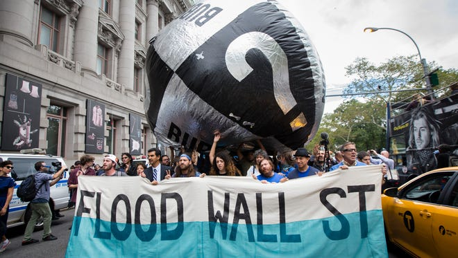 Demonstrators march toward Wall Street from New York City's Battery Park Monday to protest corporate greed.