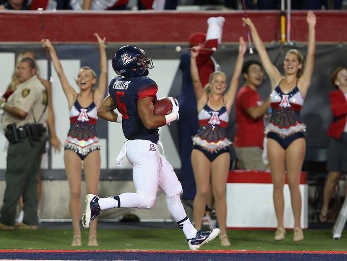 TUCSON, AZ - AUGUST 29:  Running back  Arizona Wildcats wide receiver Nate Phillips scores a touchdown against the UNLV Rebels during the first quarter of the college football game at Arizona Stadium on Aug. 29, 2014, in Tucson, Ariz.