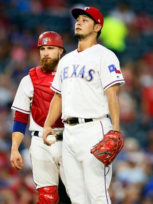 The Texas Rangers beat the trade deadline by dealing both starting pitcher Yu Darvish, right, and catcher Jonathan Lucroy.