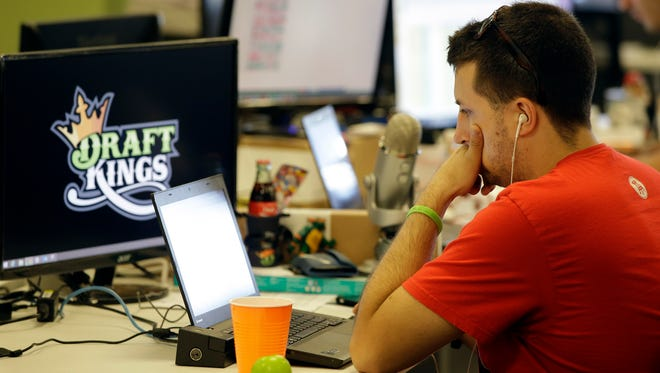 In this Sept. 9, 2015 file photo, Devlin D'Zmura, a trending news manager at DraftKings, a daily fantasy sports company, works on his laptop at the company's offices in Boston.