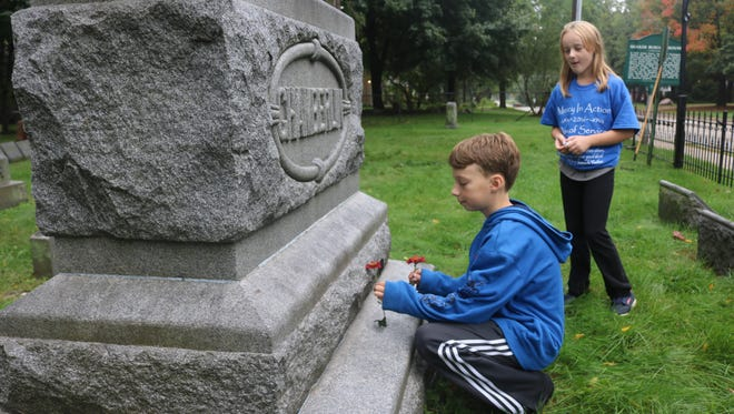 Sean Dinnan places a mum on a headstone at historic Quaker Cemetery in Farmington while his sister Evelyn looks on.