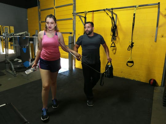 Trainer Gabino Gonzalez holds an oxygen tank for Dima Azzam as he guides her to a rest station during a workout.
