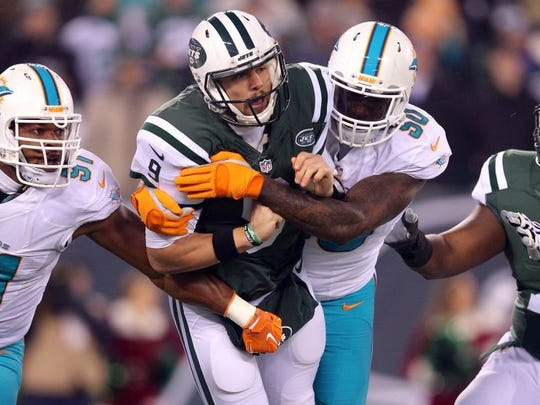 Dec 17, 2016; East Rutherford, NJ, USA; New York Jets quarterback Bryce Petty (9) is hit after throwing a pass by Miami Dolphins defensive end Andre Branch (50) during the first quarter at MetLife Stadium.