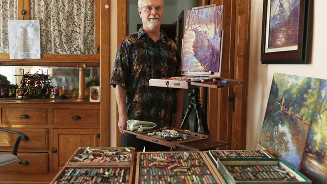 """Artist Mike Barret Kolasinski poses for a photograph with his pastel painting, titled, """"Glide to be Here,"""" at his home Aug. 13 in Chicago."""