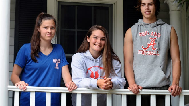 Recent Ashland High graduate Ryann Lima (center) with sister Colby and brother Jack (right) at their home in Ashland on Thursday.
