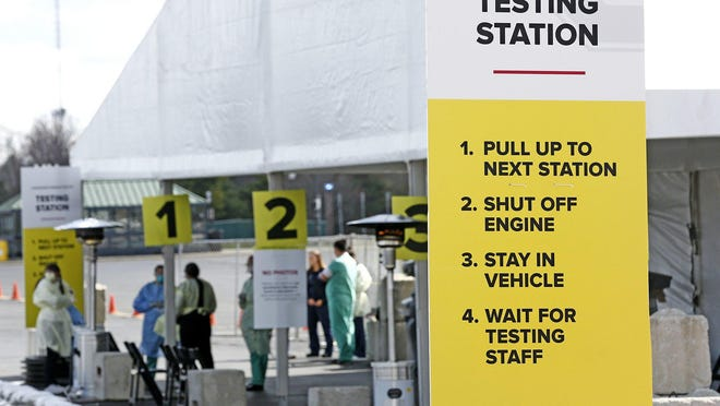 Medical personnel wait at a COVID-19 testing center for people to drive up and get tested. This site is one of two outside centers set up near the Ohio State University campus area.