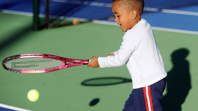 Three-year-old Colston Barnes plays tennis with his father at the John M. Phillips Tennis Complex on a sunny Wednesday afternoon.