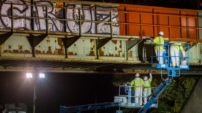 Painters work to cover graffiti on a CSX railroad bridge over Concord Avenue in Wilmington on Thursday night.