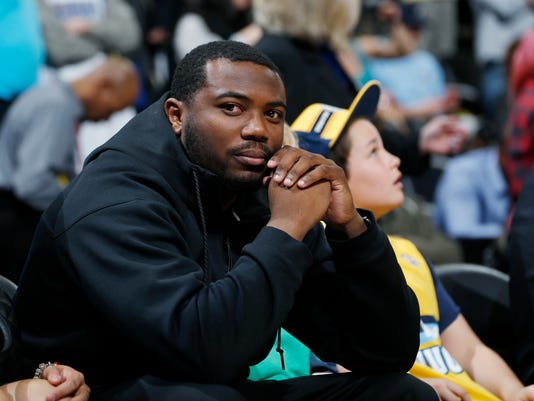 Denver Broncos running back C.J. Anderson looks on from a court side seat as the Golden State Warriors face the Denver Nuggets during the first half of an NBA basketball game, Wednesday, Jan. 13, 2016, in Denver. (AP Photo/David Zalubowski)