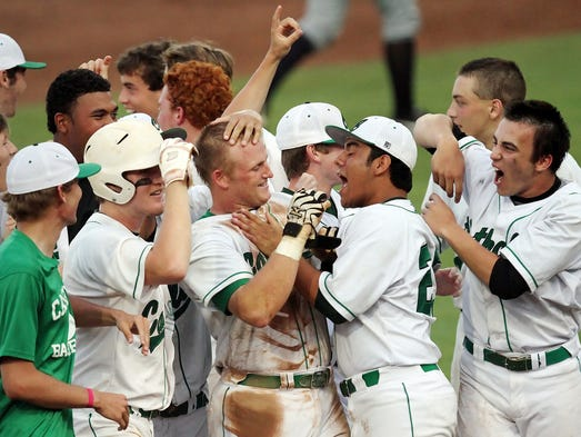 Pensacola Catholic High School's Cody Henry, center, is mobbed by teammates after he drove in the game winning run against North Broward Preparatory School on Wednesday at jetBlue Park in Fort Myers.