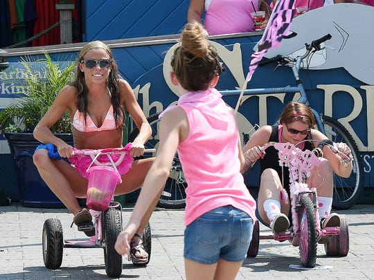 Bethany Slawick from Clayton (left) and Lisa Carey from Lewes compete at Dewey Beach's annual Big Wheels Races for Breast Cancer at The Starboard last year.