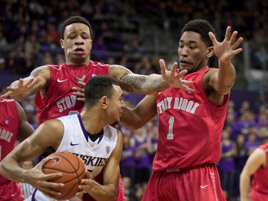 Stony Brook's Rayshaun McGrew, upper left, and Deshaun Thrower, right, defend Washington's Nigel Williams-Goss, forcing him to call a timeout Dec. 28, 2014, in Seattle. Stony Brook won, 62-57.