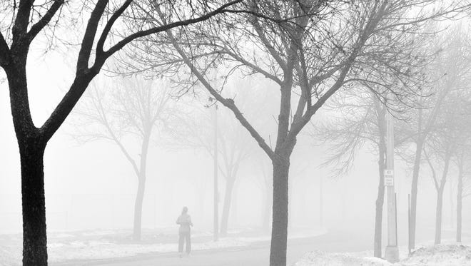 A runner gradually fades into the thick fog Dec. 14, 2014 during a jog around Whitney Park. The atmospheric feel of the fog can help to create a continuum of subtle tonal values from black to white. The fog also eliminates background distraction.