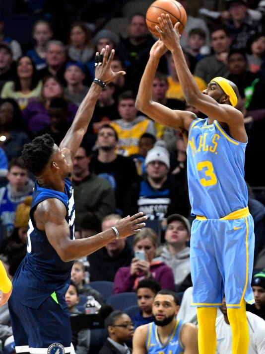 Los Angeles Lakers' Corey Brewer, right, shoots over Minnesota Timberwolves' Jimmy Butler in the first half of an NBA basketball game Monday, Jan. 1, 2018, in Minneapolis. (AP Photo/Jim Mone)