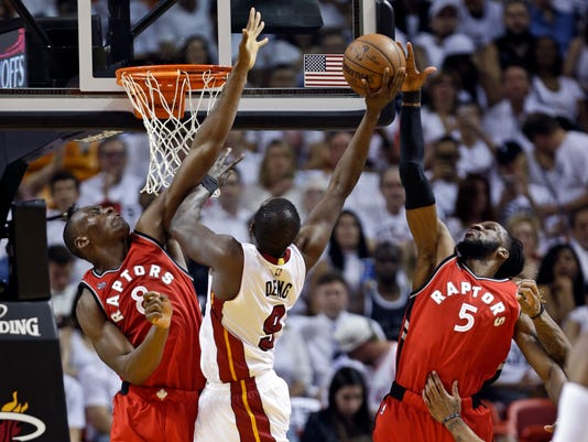 Miami Heat's Luol Deng (9) goes up to shoot between Toronto Raptors' Bismack Biyombo (8) and DeMarre Carroll (5) during the second half of Game 6 of the NBA basketball Eastern Conference semifinals, Friday, May 13, 2016, in Miami. (AP Photo/Alan Diaz)