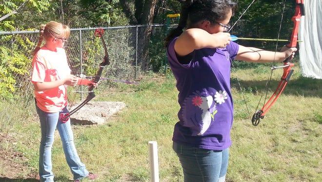 Rachel Windsor, an 8th grader at La Plata, and Paige Trevizo, a 6th grader at Cliff Schools, take aim at the targets.