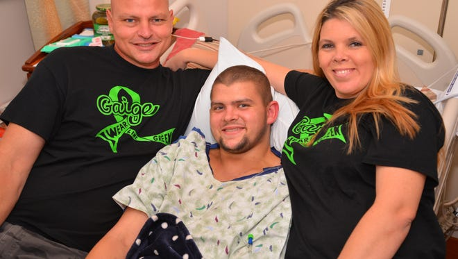 """Gaige Robbins of Melbourne is diagnosed with  nonHodgkins Lymphoma and has been undergoing chemo and radiation treatments.  His family is selling shirts that say """"Gaige. I wear lime green"""" in honor of their 19-year-old son. Gaige surrounded by his dad Shane and mom Christa."""