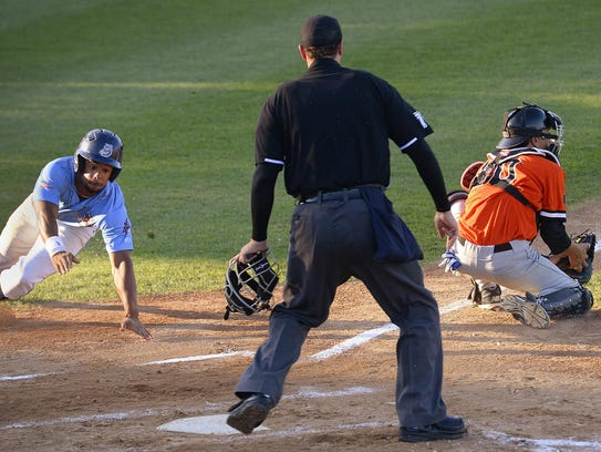 The St. Cloud Rox's Marcus Carson (5) dives for home