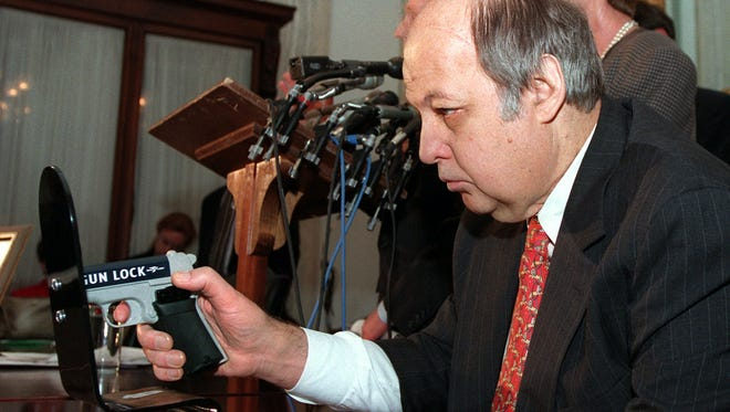 Former White House press secretary James Brady holds a model of a gun trigger lock during a news conference on Capitol Hill on March 12, 1997.