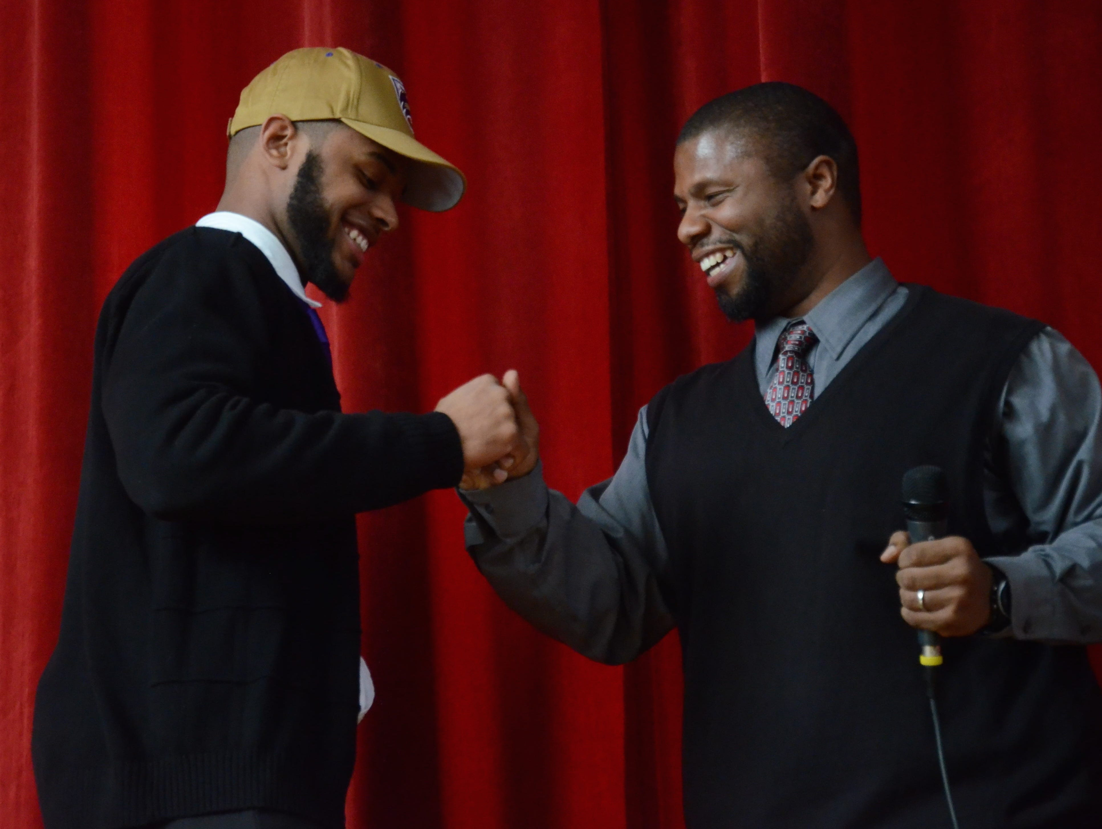 East Nashville coach Brian Waite (right) congratulates senior DeVarius Cortner prior to him signing to play football at Western Carolina.