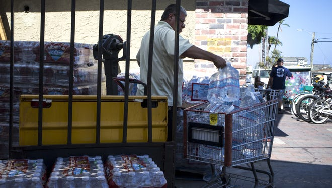EXTREME MEASURES: A Vons' employee on Catalina Island loads a cart with bottled water to restock store shelves in Avalon, Calif., where residents of the tourist town must survive on what water the city can capture from the sky and sea, plus pallet loads of bottled water.