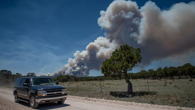 "Residents of the town of Chilili along state road 337 begin to evacuate due to the Dog Head wildfire near the Manzano mountains, Wednesday, June 15, 2016, in Chilili, N.M. Authorities don't have a containment estimate yet for a wildfire burning in the Manzano Mountains southeast of Albuquerque but say good weather helped firefighters attack the fire overnight. The so-called ""Dog Head Fire"" in part of the Cibola National Forest east of Los Lunas started Tuesday and grew to over a square mile by Wednesday morning after its growth slowed overnight."
