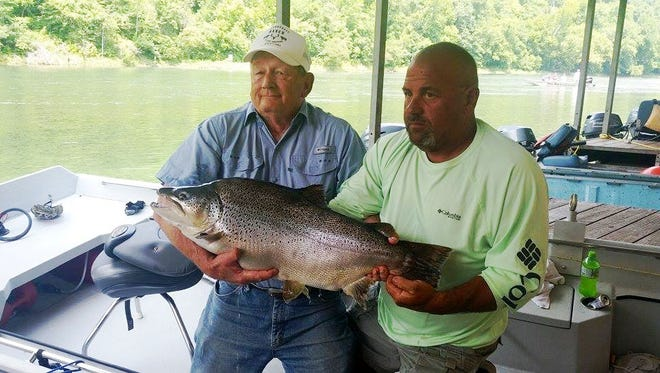 Melvin Bell, left, and Jeff Moore, local fishing guide, hold up a monster 30-pound brown trout at Bull Shoals-White River State Park on Sunday.