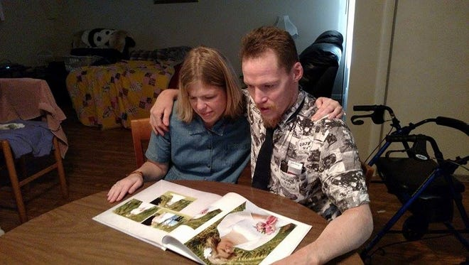 Randy Coleman and Melissa Kuhlenschmidt flip through their wedding album on a recent day at their home.