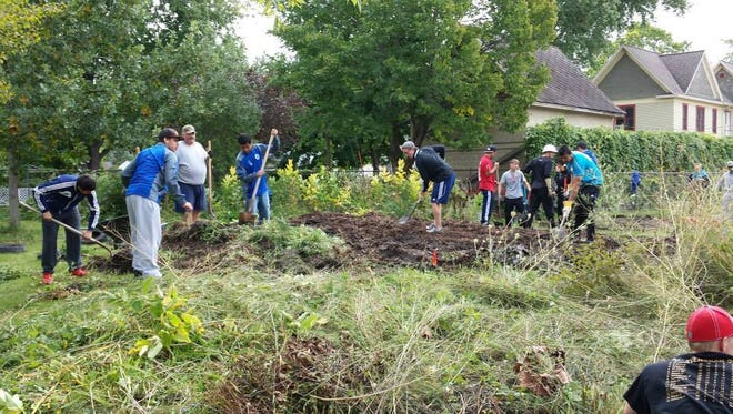Volunteers clear an overgrown plot to create a usable nature center for Chegwin Elementary School students.