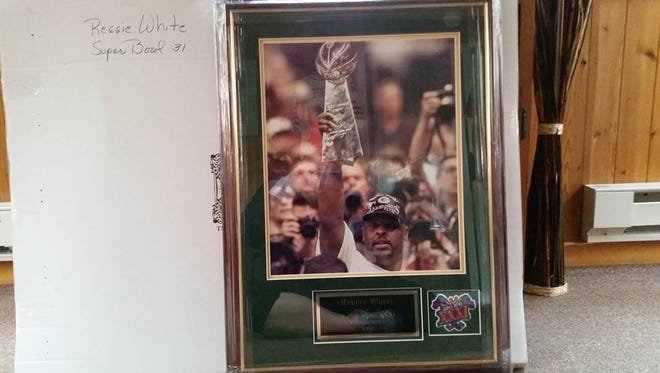 Framed and signed Reggie White photo up for auction to benefit Lynn Farr.