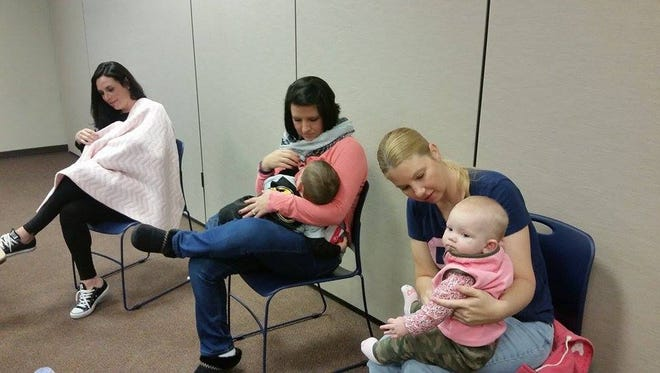 Allison Montoya, Danielle Helton, and Amy Downton nurse their children at the Northern Kentucky Breastfeeding Competition.