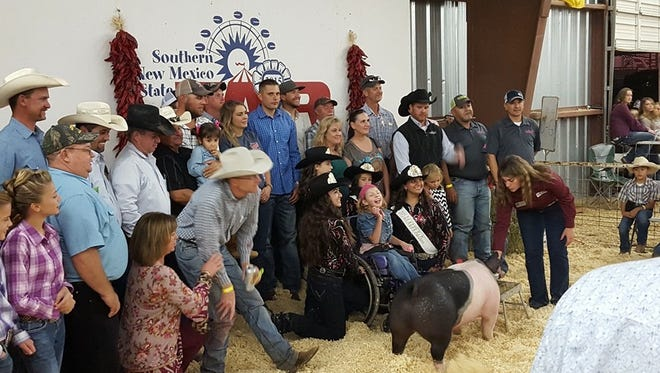 Madison Francis, 10, of Clint, Texas, poses for a photo with fairgoers and her show pig, Wobs. At the Southern New Mexico State Fair auction this year, Wobs sold for $15,000.