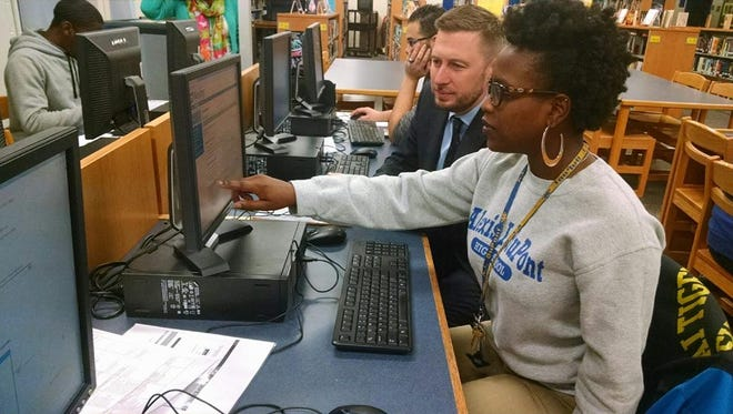 Chief Academic Officer Michael Watson, left, works with students at A.I. duPont High School during College Application Month.
