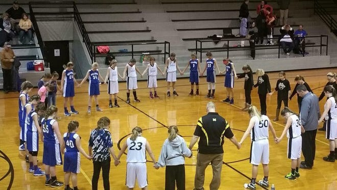 Basketball players in Shelby Eastern Schools recently prayed with coaches after a game.