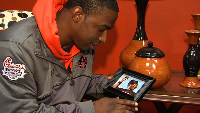 Quan Bray looks at a photo of his mother, Tonya Bray, who died his freshman year at Auburn.