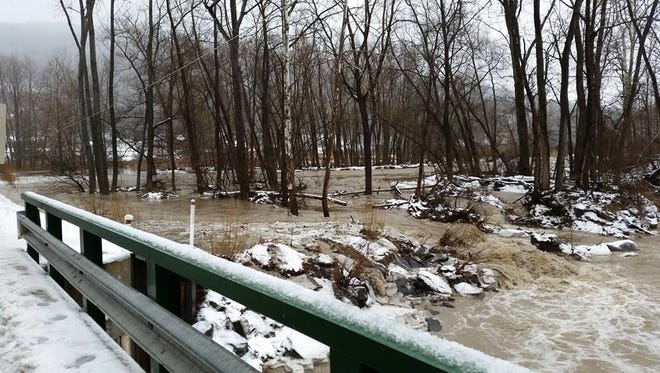 Water overflowing on the banks beneath the Carter Creek Bridge, in Newfield. Residents have been told they are responsible for clearing flood-causing debris from the state-protected waters running through their property, as the county and state have no jurisdiction.
