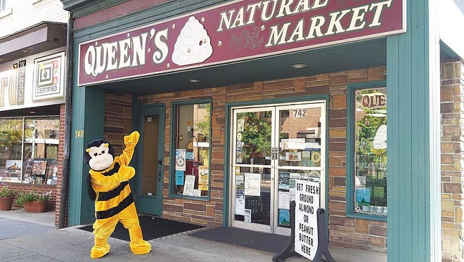 "Queen's Natural Market mascot ""Buzz"" invites customers to come shop."