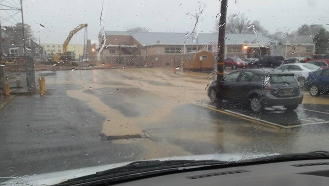 Muddy rainwater runs from the Rehoboth Beach City Hall construction site during a heavy rain Friday morning. The run-off is under investigation.