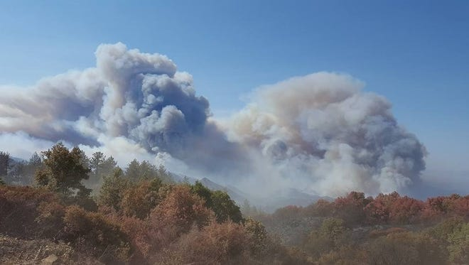 This photo provided by California Department of Forestry and Fire Protection shows smoke billowing from a wildfire near Lake Nacimiento in San Luis Obispo County, Calif., Saturday, Aug. 20, 2016.