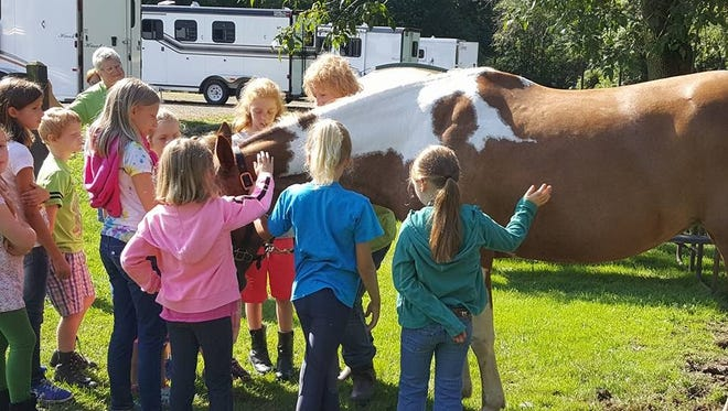 Instructor Penny Fanning introduces Rosie the Paint mare to a group of kids.